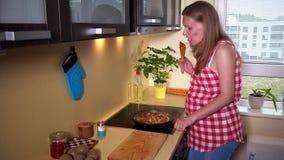Comida de mezcla de la mujer embarazada en cocinar la cacerola y la sonrisa que miran la cámara metrajes