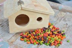 Comida de pájaro y poca casa de madera imagen de archivo libre de regalías