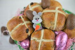 Comida de Pascua del primer con los bollos cruzados calientes frescos y la decoración linda del conejito Foto de archivo