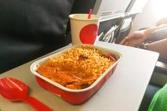 Comida del arroz de aviones simple, carne, café en utensi disponible Fotos de archivo