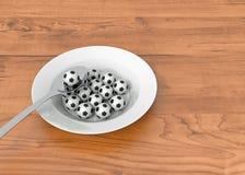 Comida del fútbol - bolas en una placa profunda en la madera Imagenes de archivo