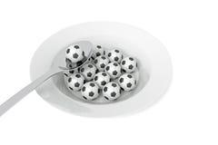 Comida del fútbol - bolas en una placa profunda en un fondo blanco Foto de archivo libre de regalías