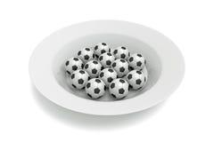 Comida del fútbol - bolas en una placa profunda en un fondo blanco Imagenes de archivo