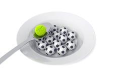 Comida del fútbol y del tenis - bolas en una placa profunda en un fondo blanco Imagen de archivo
