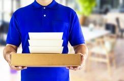Comida del servicio o de la orden de entrega de la comida en línea Hombre de entrega en azul imagenes de archivo