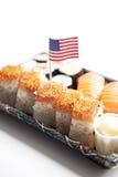 Comida del sushi en la bandeja con la bandera americana contra el fondo blanco Foto de archivo