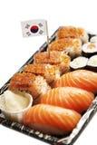 Comida del sushi en la bandeja con la bandera coreana contra el fondo blanco Imagen de archivo libre de regalías