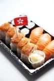 Comida del sushi en la bandeja con la bandera de Hong Kong contra el fondo blanco Imagen de archivo libre de regalías