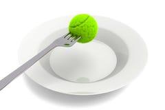Comida del tenis - pelota de tenis y bifurcación en un fondo blanco Foto de archivo libre de regalías