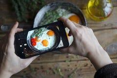 Comida del tiroteo en la cámara del ` s del teléfono, huevos fritos en una cacerola vieja con los tomates en una tabla de madera, Foto de archivo