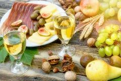 Comida deliciosa y x28; Meal& mediterráneo x29; con el prosciutto, el queso, la fruta y el vino blanco Imagen de archivo libre de regalías
