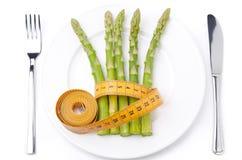 Comida dietética - espárrago envuelto con la cinta métrica en la placa Fotografía de archivo libre de regalías