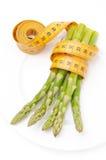 Comida dietética - espárrago envuelto con una cinta métrica Foto de archivo libre de regalías