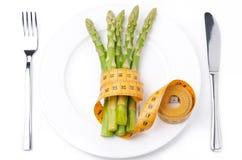 Comida dietética - espárrago envuelto con una cinta métrica Imagen de archivo