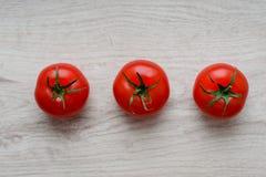 Comida ecológica y sana, aún vida de los tomates y de los pepinos frescos, maduros en el fondo de la madera Fotografía de archivo libre de regalías
