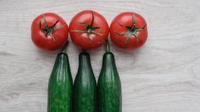 Comida ecológica y sana, aún vida de los tomates y de los pepinos frescos, maduros en el fondo de la madera Foto de archivo
