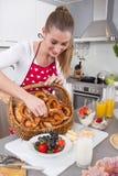 Comida en la cocina - fabricación de la porción de la mujer joven del desayuno para t Imagenes de archivo