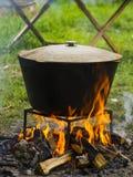 Comida en una caldera en un fuego El cocinar al aire libre en caldera del arrabio Imagen de archivo libre de regalías