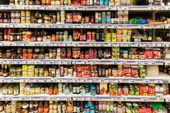 Comida enlatada y salsas especiales en soporte del supermercado fotos de archivo