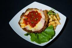 Comida especial con las patatas fritas, la ensalada y un escalope fotografía de archivo