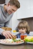 Comida feliz de la porción del padre al hijo en la tabla en cocina Foto de archivo libre de regalías
