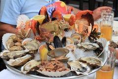 Comida fría de los mariscos con las ostras frescas, almejas, cangrejos, camarones, caracoles Foto de archivo libre de regalías