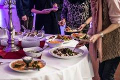 Comida fría del abastecimiento del grupo de la gente en el restaurante de lujo de la tabla de la comida con la carne, el pan y di Imágenes de archivo libres de regalías