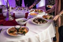 Comida fría del abastecimiento del grupo de la gente en el restaurante de lujo de la tabla de la comida con la carne, el pan y di Fotografía de archivo