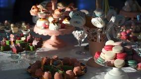 Comida fría del caramelo de la boda Barra del postre cubierta con diversas tortas coloridas y deliciosas, los torta-estallidos, l almacen de metraje de vídeo