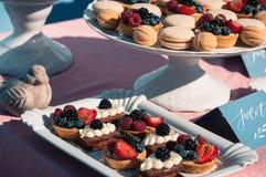 Comida fría dulce deliciosa con las magdalenas, macarrones, otros postres, Fotos de archivo libres de regalías
