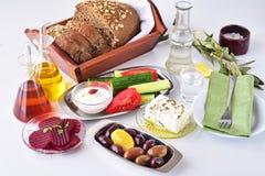 Comida griega, mezedes Tarros con el aceite de oliva y el vinagre de la vid, aceitunas, queso Feta, tzatziki, pan oscuro, raki, r fotos de archivo libres de regalías
