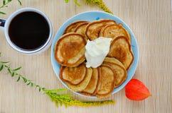 Comida hecha en casa - buñuelos fritos con la harina de centeno con crema agria y una taza de café Adornado con las flores y el p Imagen de archivo libre de regalías