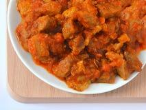 Comida hecha en casa: carne guisada con las zanahorias, las cebollas y la paprika en una placa blanca imagen de archivo libre de regalías