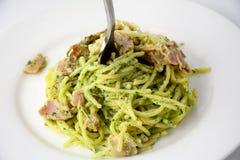 Comida italiana: espaguetis con pesto y tocino Fotografía de archivo