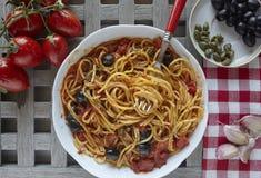 Comida italiana: pastas con los tomates, aceitunas y alcaparras, llamadas puestas Fotografía de archivo