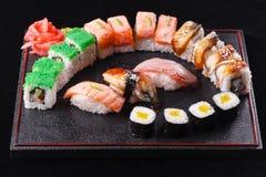 Comida japonesa, sabrosa de la comida para el almuerzo Mariscos Sushi con la anguila, salmón, trucha, fondo negro del atún Imagenes de archivo