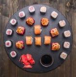 Comida japonesa, sushi con los salmones y atún, rollo de Philadelphia, y sushi cocido, jengibre fresco y palillos, soja, presenta Fotos de archivo libres de regalías