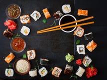 Comida japonesa tradicional - sushi, rollos y salsa en un fondo oscuro imagen de archivo
