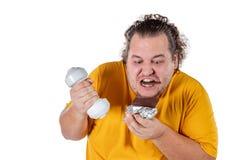 Comida malsana antropófaga gorda divertida y el intentar tomar el ejercicio aislado en el fondo blanco foto de archivo