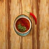 Comida marroquí, plato de sopa del tomatoe adornado con perejil, en una placa con pimienta de chile candente, en una tabla de mad imagen de archivo