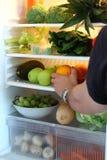 Comida masculina de la cosecha de la mano del refrigerador imagenes de archivo