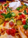 Comida mexicana - nachos con queso, crema agria y desmoches derretidos Fotografía de archivo
