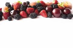 Comida negra y roja Zarzamoras, fresas, ciruelos y melocotones maduros en el fondo blanco Bayas en la frontera de la imagen con l Foto de archivo libre de regalías