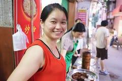 Comida no identificada de la venta de la mujer en el mercado Foto de archivo libre de regalías