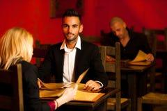 Comida ordeting de los pares jovenes en menú de la lectura del restaurante Imágenes de archivo libres de regalías