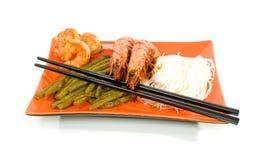 Comida oriental en la placa anaranjada Imagenes de archivo