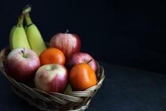 Comida oscura - el claroscuro mezcló la fruta en cesta de mimbre imagen de archivo