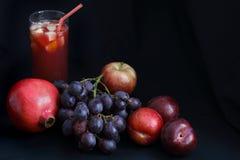 Comida oscura - granada, uvas, manzana y ciruelos del claroscuro con el ponche de fruta imagenes de archivo