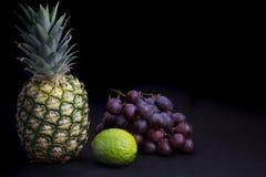 Comida oscura - iluminación del claroscuro en la piña, las uvas y la cal imagenes de archivo