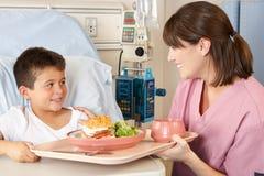 Comida paciente del niño de la porción de la enfermera en cama de hospital Imagen de archivo libre de regalías